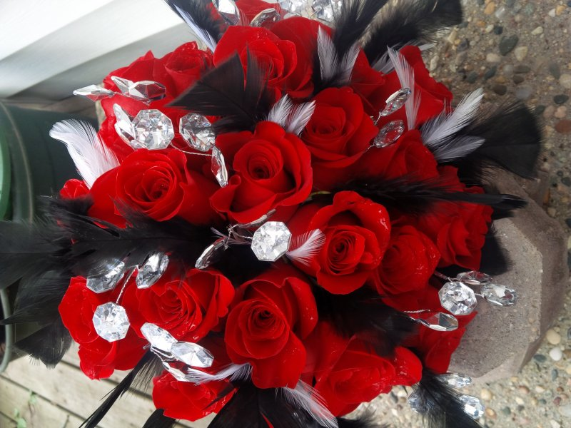 Bouquet of red roses with black and white feathers and diamond wrap and bling throughout