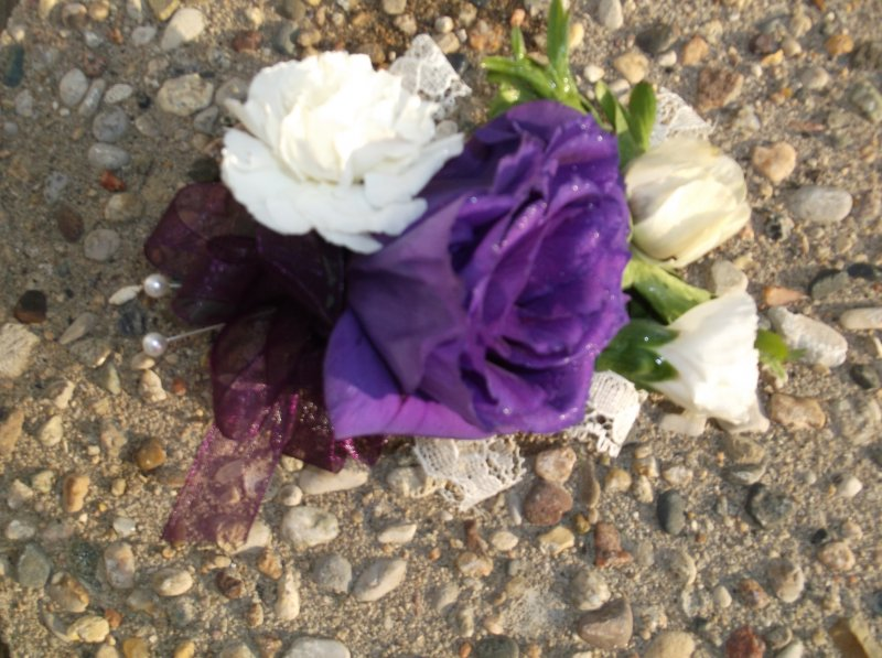 Fresh corage with purple lizzy, mini white carnations and lace detail